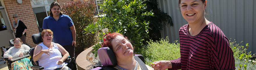 happy people, some in wheelchairs, in a garden