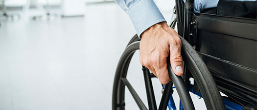 A cropped image of a person in a wheelchair shot from down low, only showing part of the wheel and the person's hand on the wheel