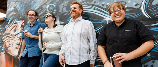 Four people leaning on a wall, smiling