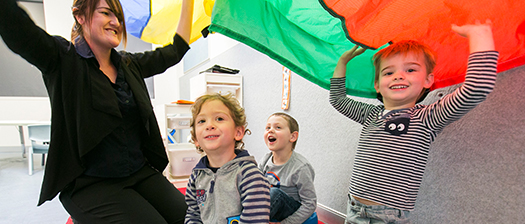 A support worker and children playing with a parachute