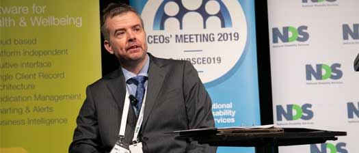 Dr Ben Gauntlett on the stage, talking at the NDS CEOs' meeting 2019