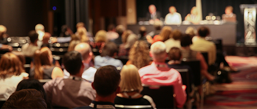 Image of the back of a crowd at a conference