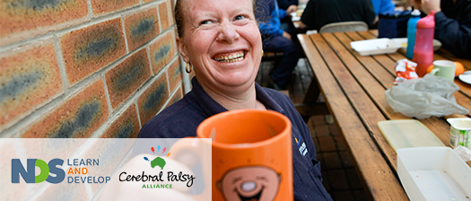 A worker holding a smiling face mug up to the camera and grinning.