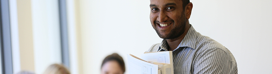 man looking at the camera and smiling while holding folders