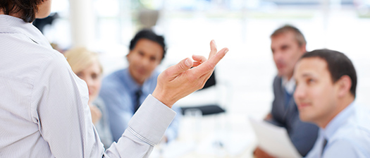 Colleagues in a meeting. Woman gesturing to colleagues with hand.