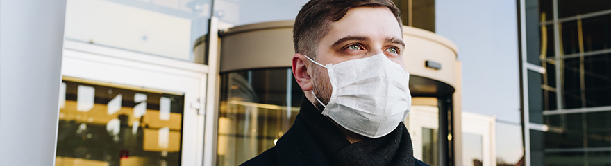 Image of man wearing surgical mask standing in front of office building