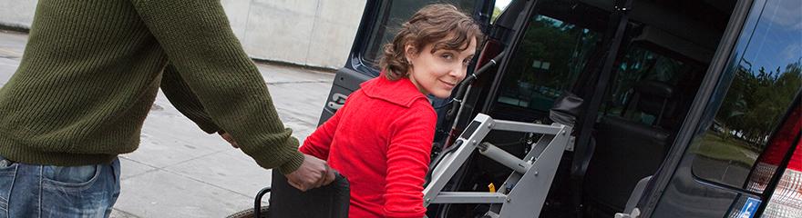Man pushing woman in wheelchair on to transport ramp