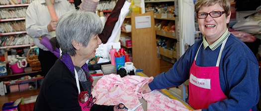 Two people working and smiling in a fabric shop