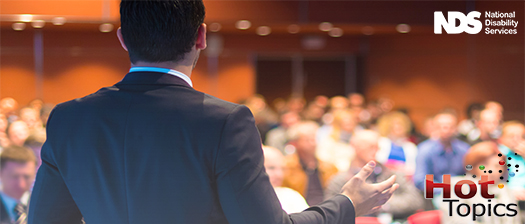 A speaker stands in front of a conference crowd