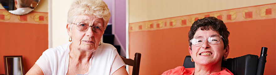 Carer sitting with client at the kitchen table