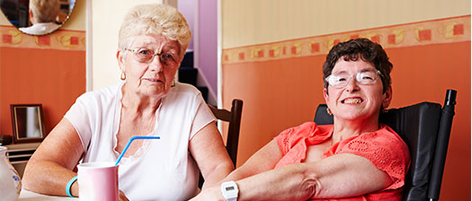 Two older people enjoying a pot of tea together.