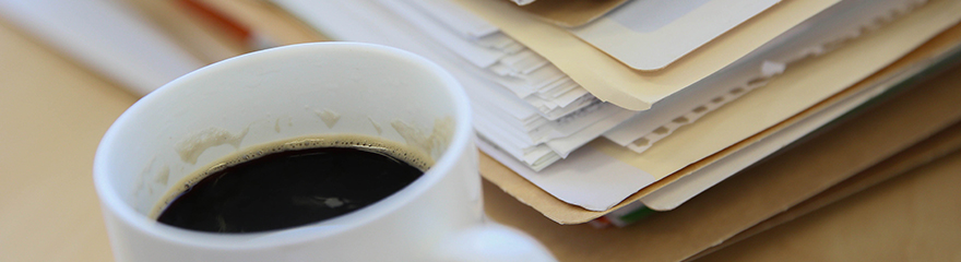 Cup of coffee next to a pile of paperwork