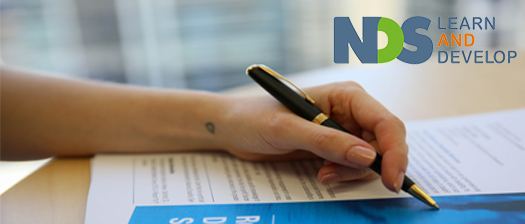 Hand holding a pen pointing to documents on a desk