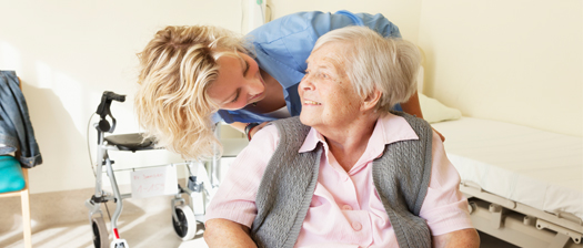 Elderly woman in wheelchair smiling and looking at worker assisting her.