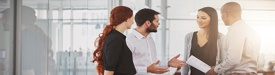 people standing in an office setting having a conversation