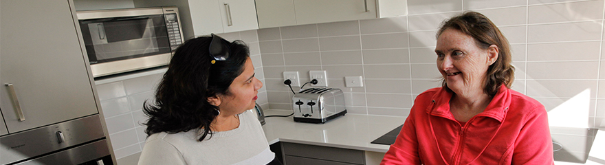 two women having a conversation in the kitchen