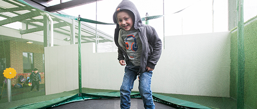 Child jumping on a trampoline and smiling