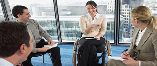 Colleagues meeting together having a discussion . Woman in a wheelchair smiling and gesturing with her hands