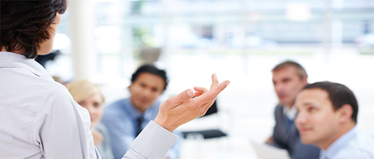 Woman speaking to colleagues pointing and gesturing with her hand.