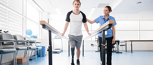 Physiotherapist supporting someone to walk with handrails