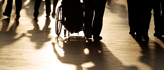 Ground view of feet and wheelchair in a crowd with shadows