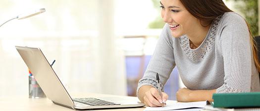 Woman using her laptop, smiling