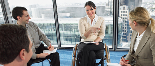 four business colleagues appear to be in discussion. Woman in wheelchair gesturing with her hands and smiling.