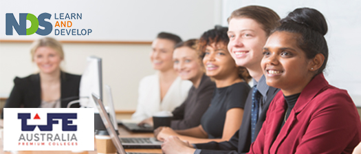 Students sitting in a classroom with laptops and smiling