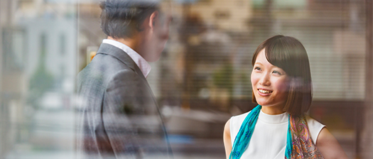 person with blue scarf looking and conversation with another individual in a business suit