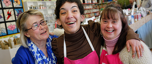 Image of three happy people dressed in aprons embracing
