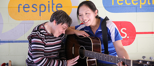 Support working assisting a person with disability to play guitar