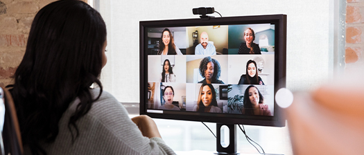 A rear view of a person looking at a monitor showing other people in an online meeting
