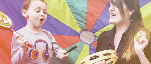 A child and an adult playing music and singing together.