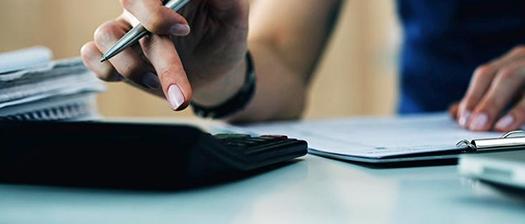 person using a calculator on desk