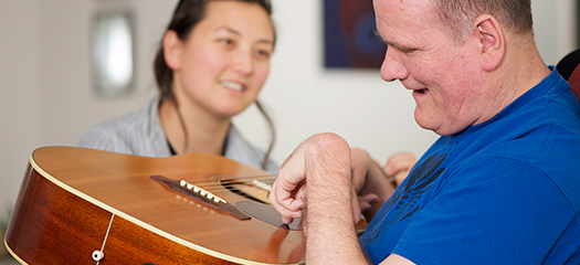 A female support worker and a male person with disability holding a guitar