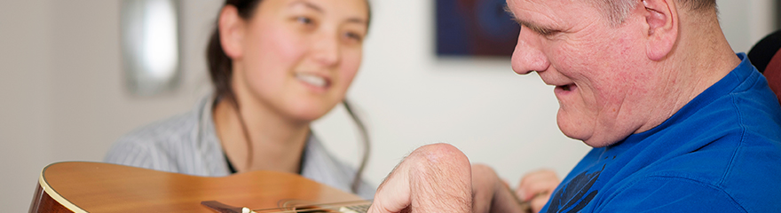 Support worker and client playing a guitar