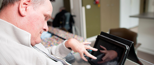 A person with disability typing on a tablet.