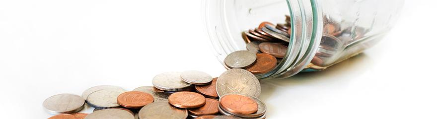 Jar of coins spilt on counter