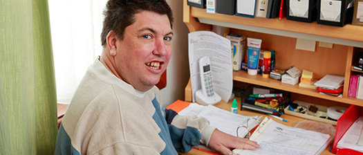 Person smiling at a home desk