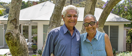 Picture of a man with his arm around a woman, with houses in the background