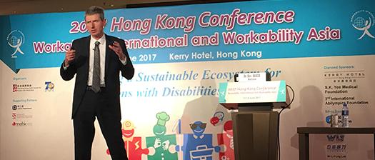 Ken delivering a speech in Hong Kong