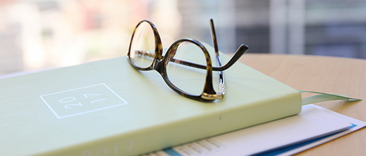 Pair of glasses resting on a diary on an office desk