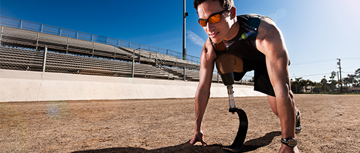 Person poised at a starting line, about to sprint, with a prosthetic foot