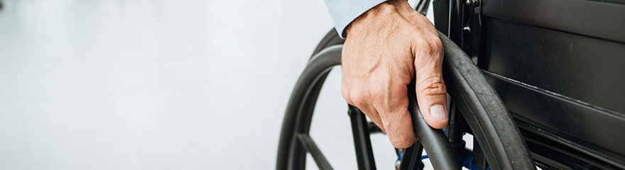 partial view of wheelchair with a hand