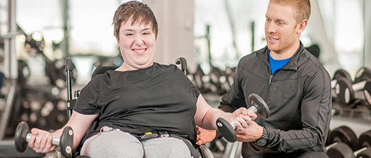 A person in a wheelchair training at the gym with a personal trainer.