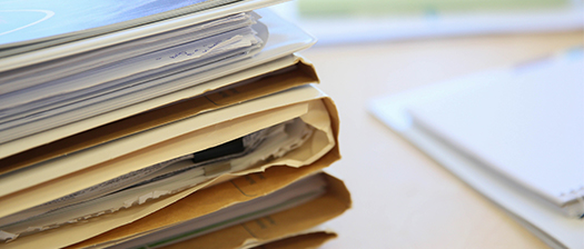 A stack of papers in different folders laying on a desk