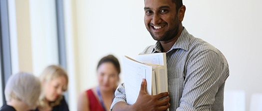 Person smiling and holding a folder, with colleagues in the background