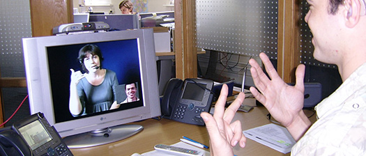 A person at work communication via signing over video connection.