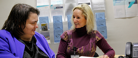 Two people doing paperwork and smiling