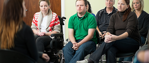 An image of a small group of people listening to a speaker